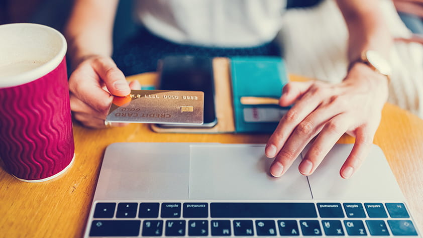 Woman sitting at her laptop paying for purchases online with her credit card