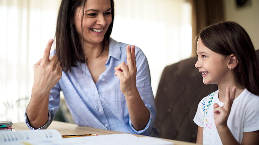 Woman talking to a young girl and crossing her fingers