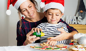 Mother and young son wearing Santa hats and decorating cookies