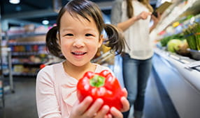 Close Up of Asian Girl Holding Red Pepper in Grocery Store