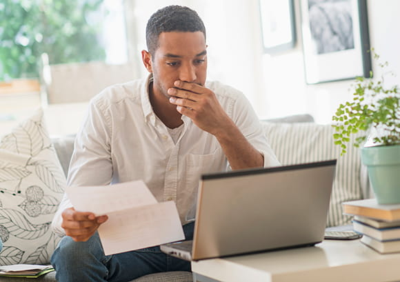 Concerned African American Male Reviewing Financial Statement