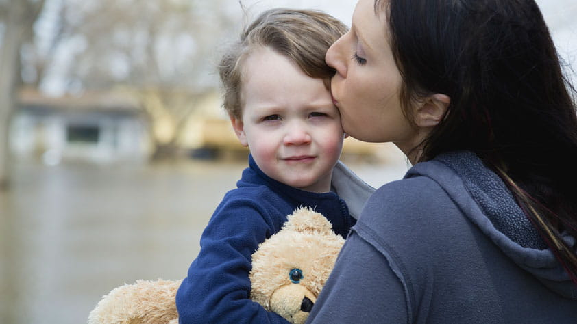 Mother Carrying Son and Standing in Flooded Town - How to Prepare for and Recover From a Natural Disaster