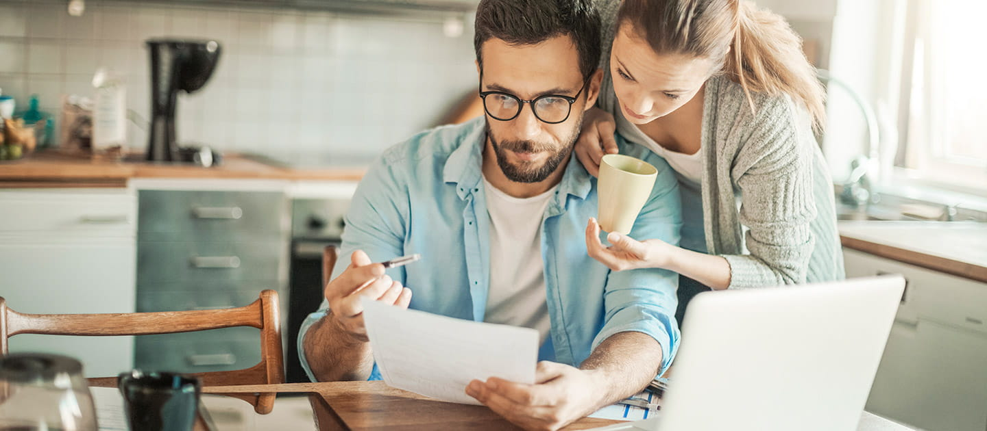 Couple looking at their laptop and discussing financial paperwork