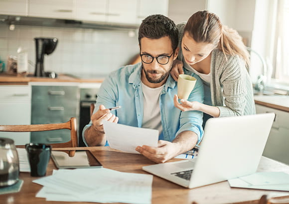 Caucasian Couple Reviewing Finances in Kitchen