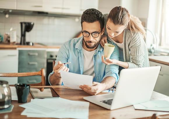 Caucasian Couple Reviewing Finances in Kitchen