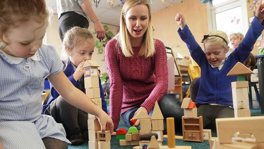 Teacher and young students stacking wooden blocks in a school classroom