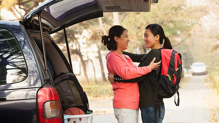 Mother and daughter embracing behind a car full of her things on a college campus