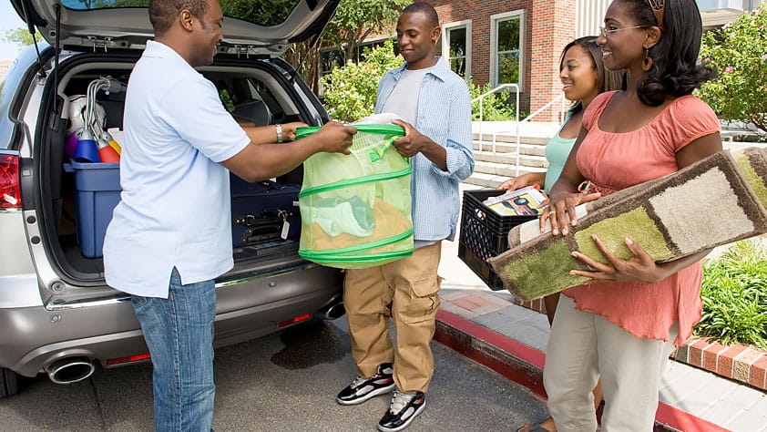 Family helping their son move into a college dorm