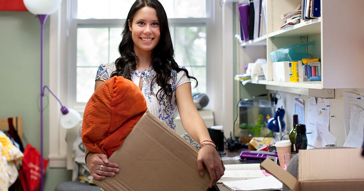 Young woman holding a box and moving into her college dorm room