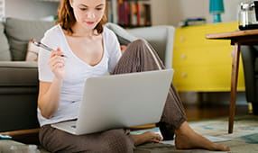 Woman Sitting on Floor with Laptop on Lap