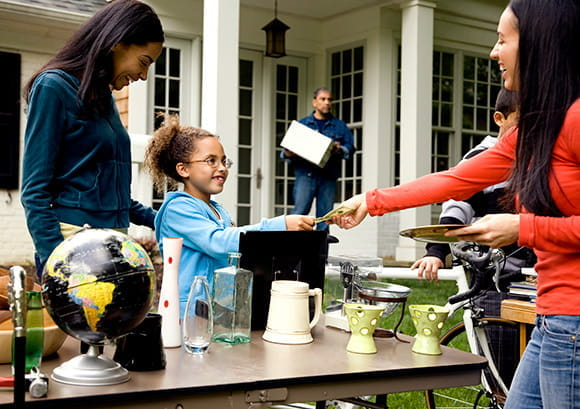 Young Girl Accepting Cash Payment at Yard Sale