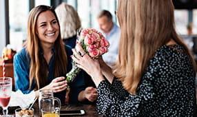 Woman Receiving Bouquet of Flowers from Female Friend