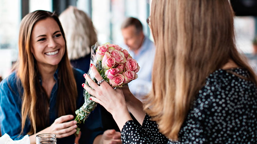 Woman Receiving Bouquet of Flowers from Female Friend