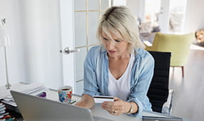 Woman at Home Office Desk Adding Credit Card Payment Online