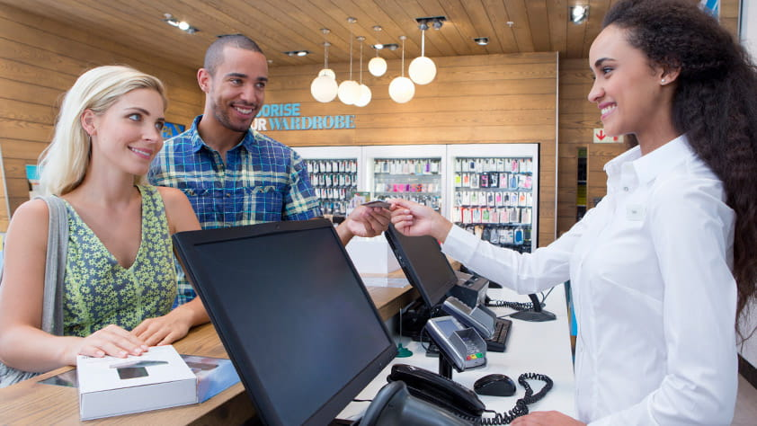 Couple making a purchase from a store assistant
