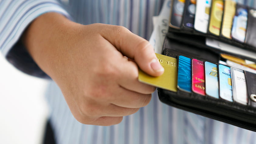 Close-up of a woman's hand pulling a credit card out of her wallet