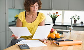 Middle Aged Woman Reviewing Finances in Kitchen