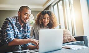 African American Couple Smiling Reviewing Laptop Screen