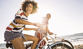 Female Friends on Beach Bike Ride
