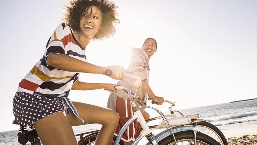 Couple riding bikes on the beach