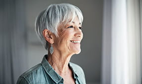 Senior Woman Smiling Staring Out Window