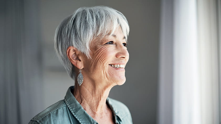 Confident senior woman looking out the window at home