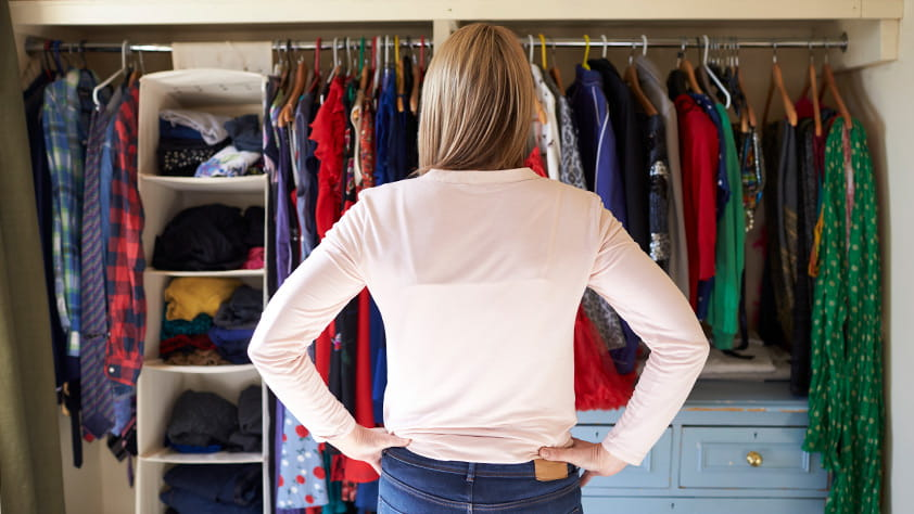 Woman with hands on hips staring into her closet