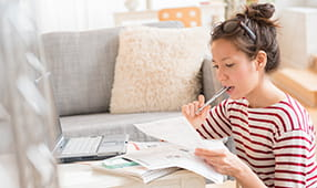 Woman Biting Pen While Reviewing Financial Statement