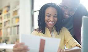 Test Your Credit Score Smarts - Couple Reading Financial Paperwork