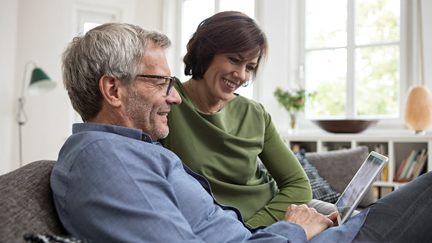 Middle Aged Couple on Couch Looking at Tablet