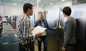 Saleswoman helping a couple shopping for a refrigerator in an appliance store