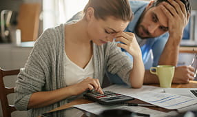 Concerned Couple Looking Through Paperwork and Using a Calculator