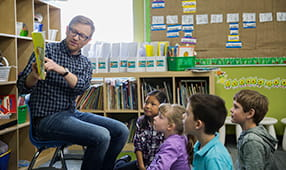 Male Elementary Teacher Reading Story to Children