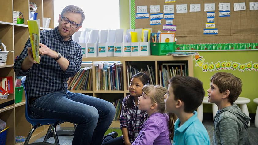 Male Elementary Teacher Reading Story to Children