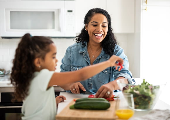 Mother and daughter preparing vegetables for lunch in the kitchen