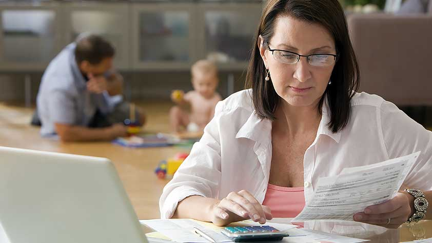 Tips to Help Teachers Manage a Financial Emergency - Woman Calculating Bills with Her Family Playing in the Background