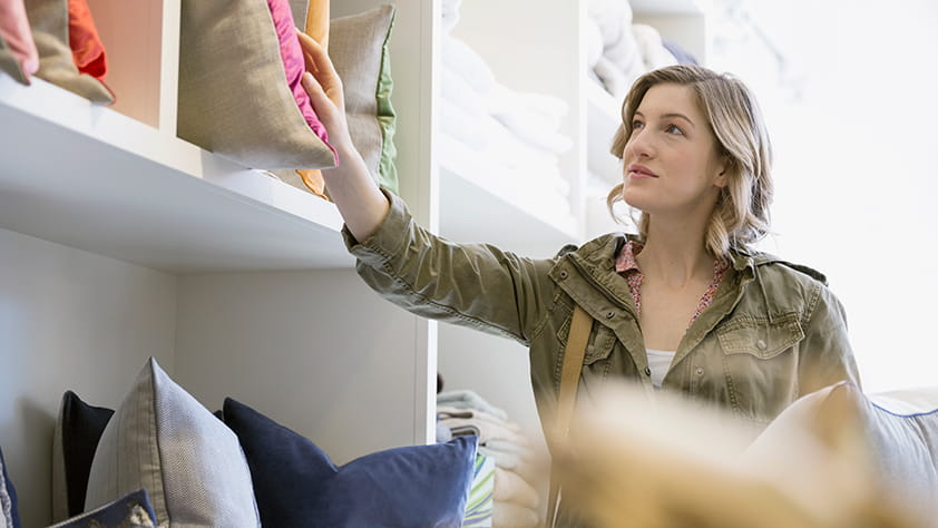 Top Teacher Discounts - Woman Buying Decorative Pillows in a Home Goods Store