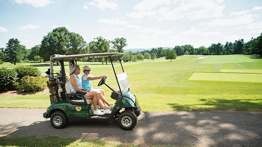 Women Driving Golf Cart on Course
