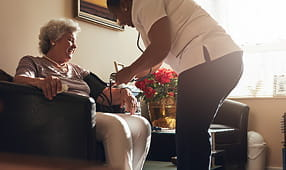 Female nurse measuring elderly woman's blood pressure