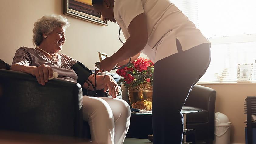 Female nurse measuring elder's woman blood pressure