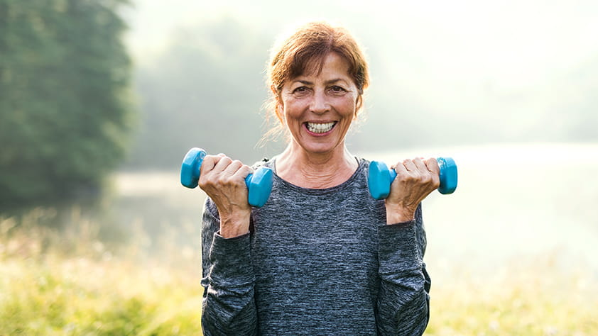 Senior woman lifting small blue hand weights outdoors