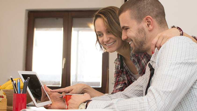 Couple Smiling Looking at Tablet