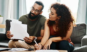 Couple Reviewing Financial Paperwork at Home