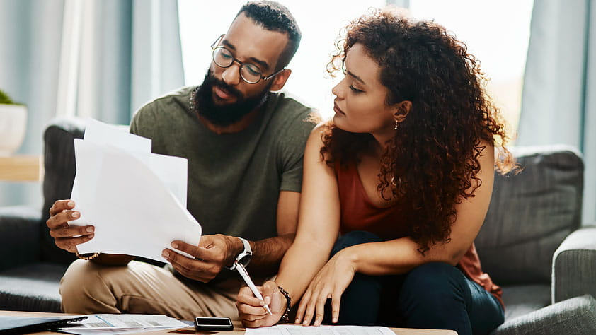 A Beginner's Guide to the Stock Market - Couple Reviewing Financial Paperwork at Home