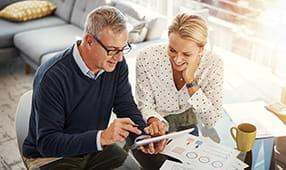 Caucasian Couple Smiling Reviewing Finances