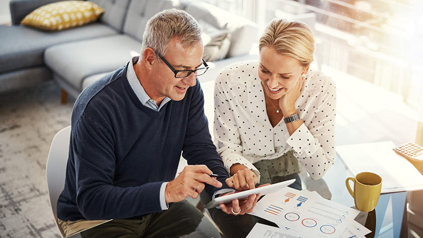 Mature couple using a digital tablet while going through financial paperwork at home