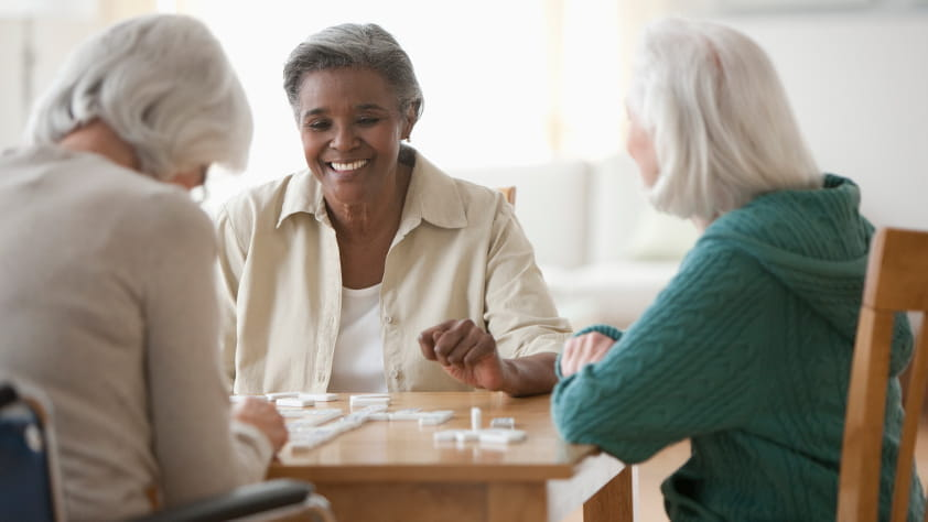 Senior women sitting at a table and spending time together playing dominoes