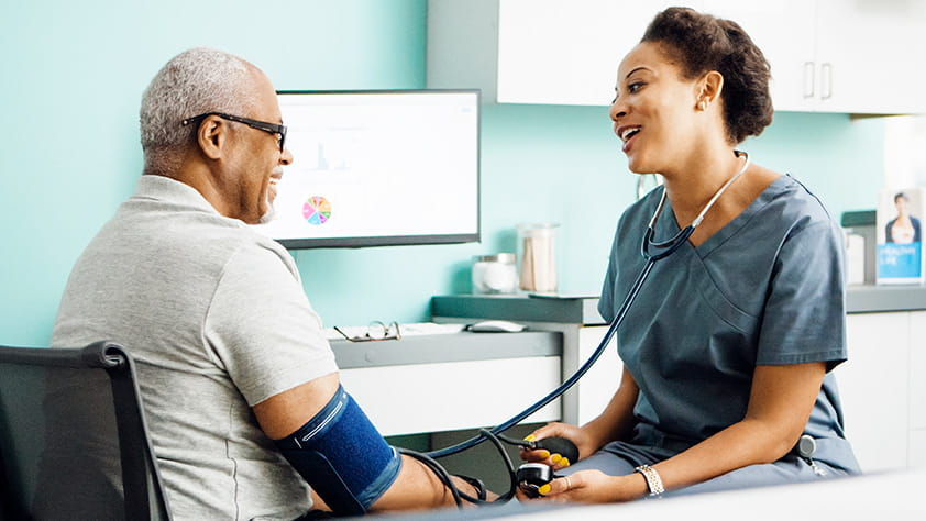 Happy female doctor checking an older male patient's blood pressure