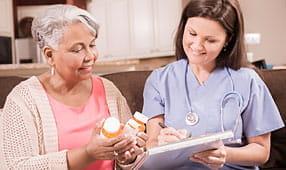 Home Healthcare Nurse Explains Medications to Senior Adult Woman