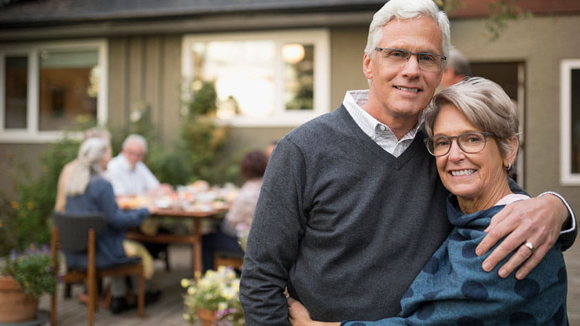 Smiling senior couple hugging as their friends have lunch on their patio in the background
